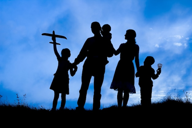 Família feliz à beira-mar na silhueta da natureza