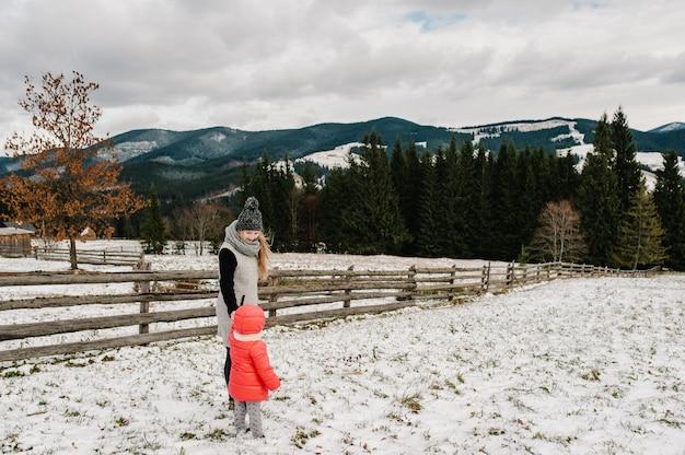 Família feliz: a mãe e a filha estão se divertindo e brincando no inverno nevado, andar na montanha, natureza. filha de mãe e filhos, desfrutando de viagem. frost inverno.