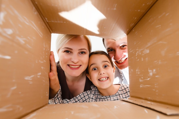 Família feliz abrindo caixa de papelão - conceito móvel