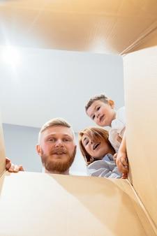Família feliz acaba de se mudar para casa nova e olhar para a caixa