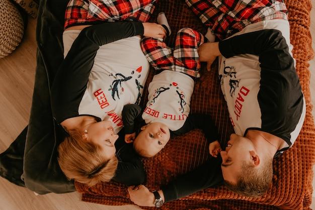 Família feliz alegre de pijama com criança deitar na cama no quarto. roupas de família de ano novo parece outfits. presentes de celebração do dia dos namorados