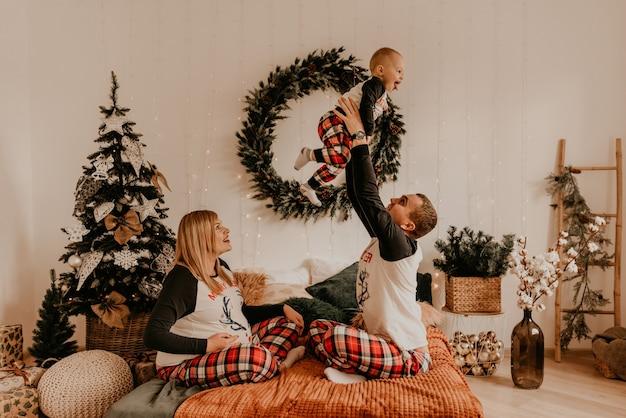 Família feliz alegre de pijama com uma criança beijando na cama no quarto. roupas de família de ano novo parece outfits. presentes de celebração do dia dos namorados