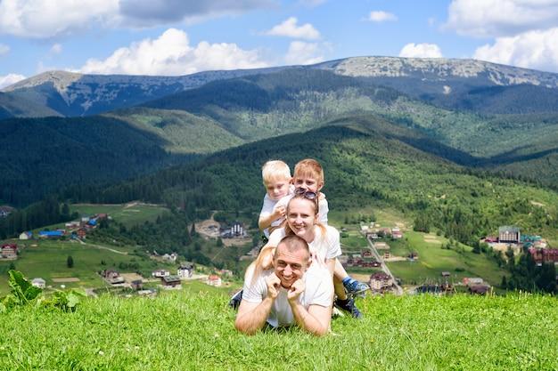 Família feliz: alegre pai, mãe e dois filhos estão mentindo grama verde contra a floresta, montanhas e céu com nuvens.