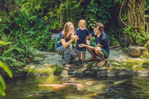 Família feliz alimentando bagres coloridos em lago tropical