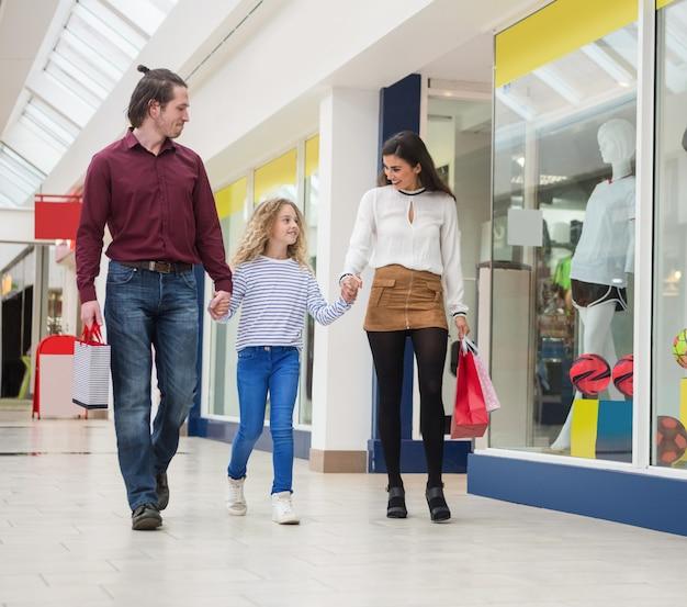Família feliz andando com sacolas de compras