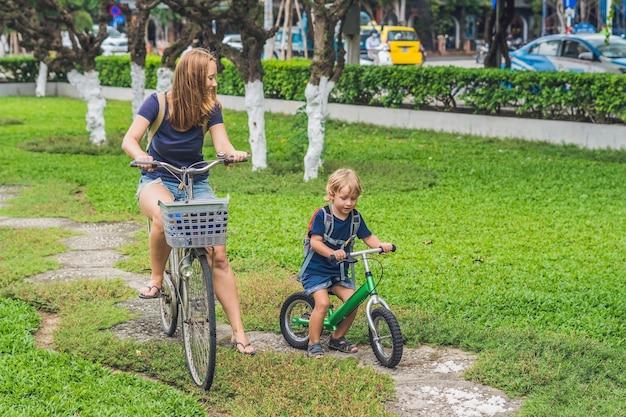 Família feliz andando de bicicleta ao ar livre e sorrindo