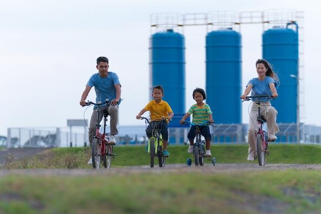 Família feliz andando de bicicleta ao ar livre, pais ativos com filhos se divertindo, esportes e exercícios em família, férias, relaxe no campo