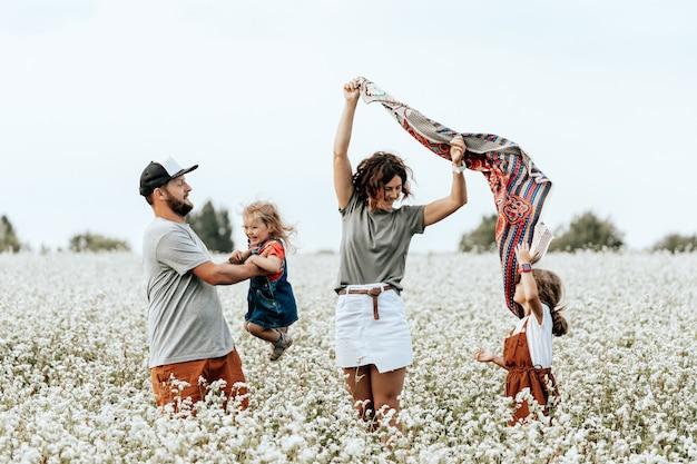 Família feliz andando em campo, brincando e curtindo o dia de verão.