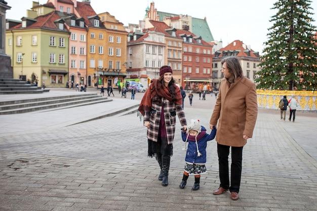 Família feliz andando na cidade de outono e se divertindo