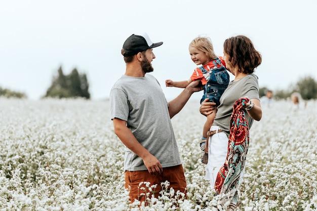 Família feliz andando no campo, jogando e aproveitando o dia de verão. livestyle andando conceito