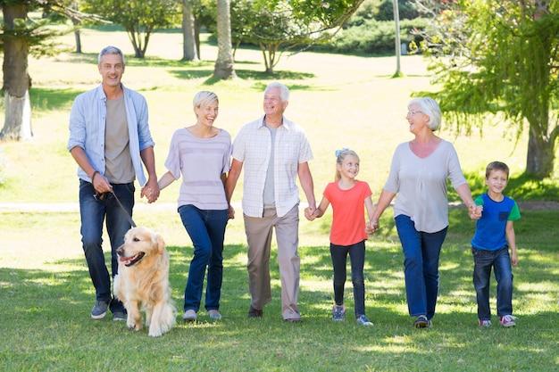 Família feliz andando no parque com seu cachorro