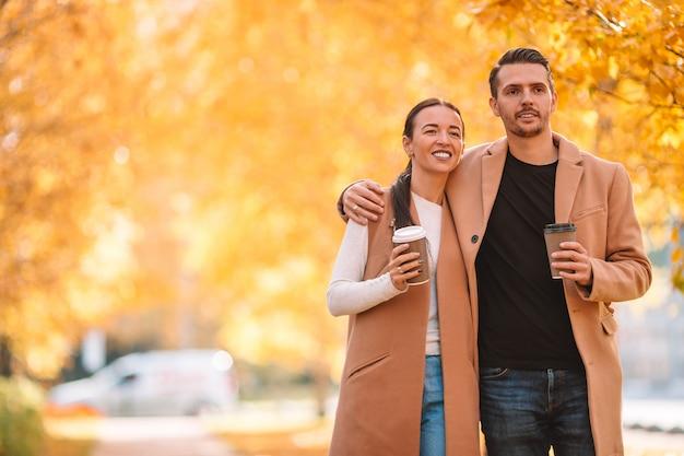 Família feliz andando no parque no dia ensolarado de outono