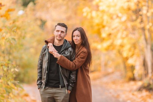 Família feliz andando no parque outono em dia ensolarado de outono