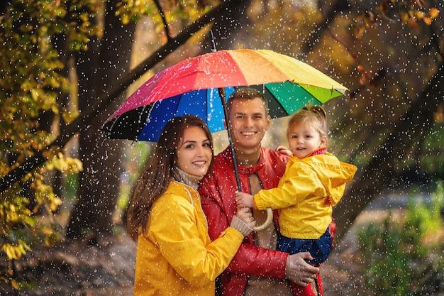 Família feliz andando sob a chuva no parque outono