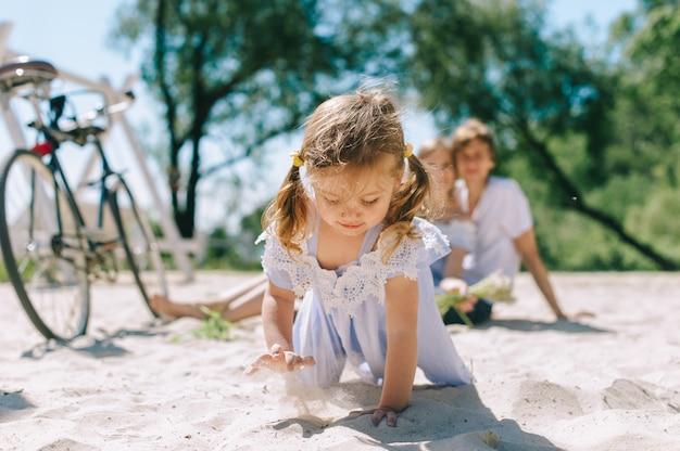 Família feliz ao ar livre a passar tempo juntos. pai, mãe e filha estão se divertindo e correndo na praia