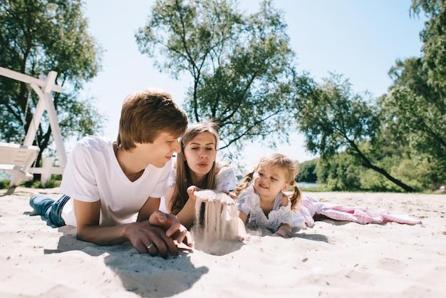 Família feliz ao ar livre a passar tempo juntos. pai, mãe e filha se divertem e brincando na praia