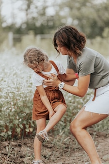 Família feliz ao ar livre. mãe ajuda e apoia a filha no campo. livestyle andando conceito