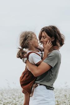 Família feliz ao ar livre. mãe e filha abraçando e se olham no campo. livestyle andando conceito