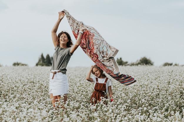 Família feliz ao ar livre. mãe e filha andando e em campo. mulher em um lenço em desenvolvimento. livestyle andando conceito