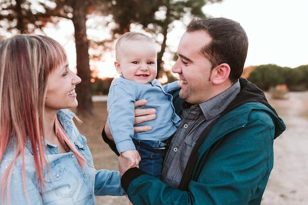 Família feliz ao ar livre no pôr do sol, pai, mãe e filho no parque. conceito de família