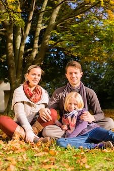 Família feliz, ao ar livre, sentado na grama no outono