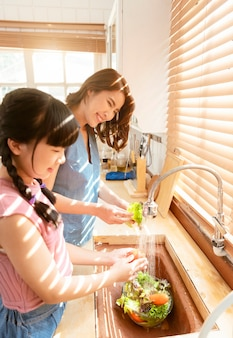 Família feliz asiática mãe e filha lavando a preparação da refeição de legumes juntos na cozinha.