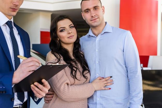 Família feliz assinando contrato com revendedor no salão