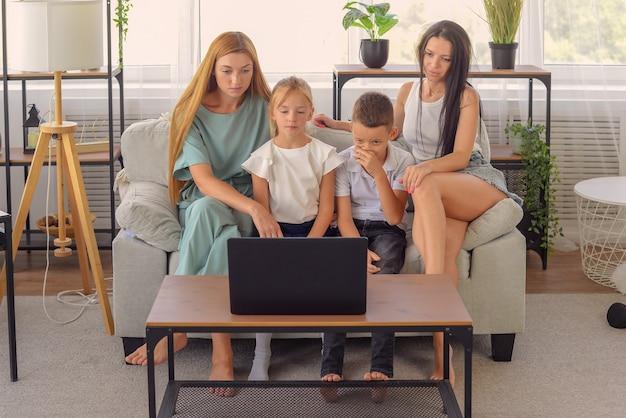 Família feliz assistindo filme juntos no laptop em casa felizes juntos