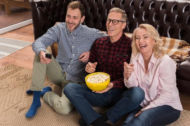 Família feliz assistindo tv e comendo pipoca