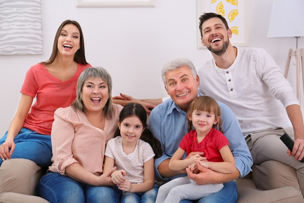 Família feliz assistindo tv no sofá em casa