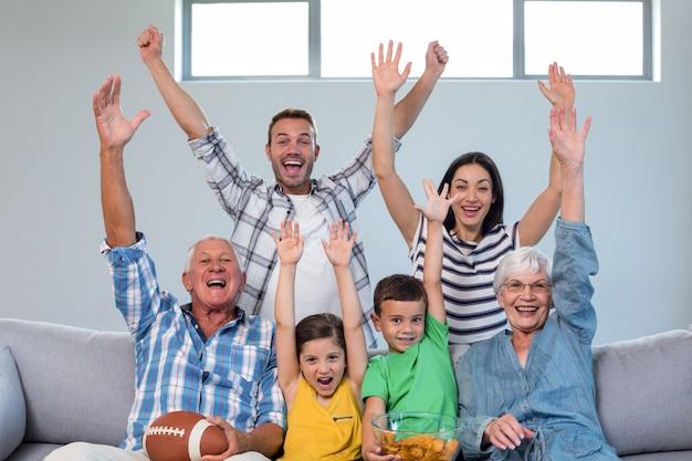 Família feliz assistindo uma partida de futebol em casa