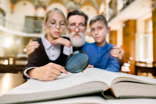Família feliz, avô e netos, professor e alunos, sentados à mesa na biblioteca e lendo um livro usando lupa. concentre-se na mão com vidro