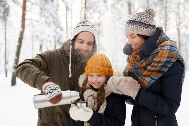 Família feliz bebendo chá inverno