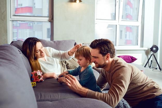 Família feliz brincando com a criança junto na sala.