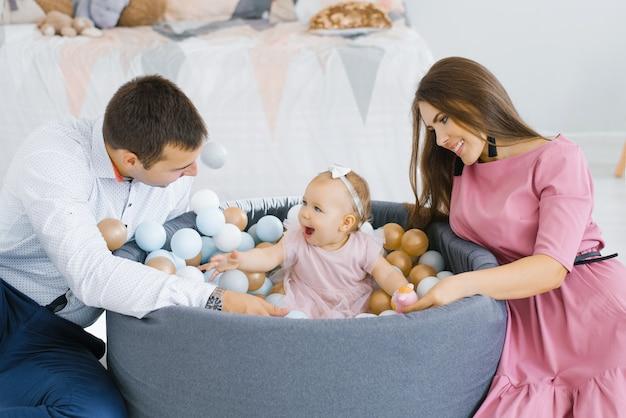 Família feliz brincando com balões coloridos no quarto das crianças em casa