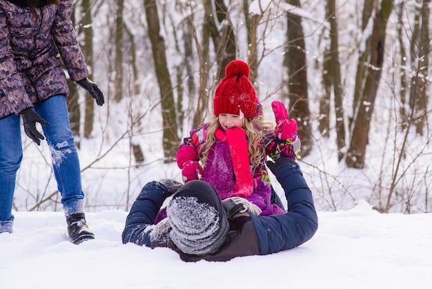 Família feliz brincando com neve na floresta de inverno
