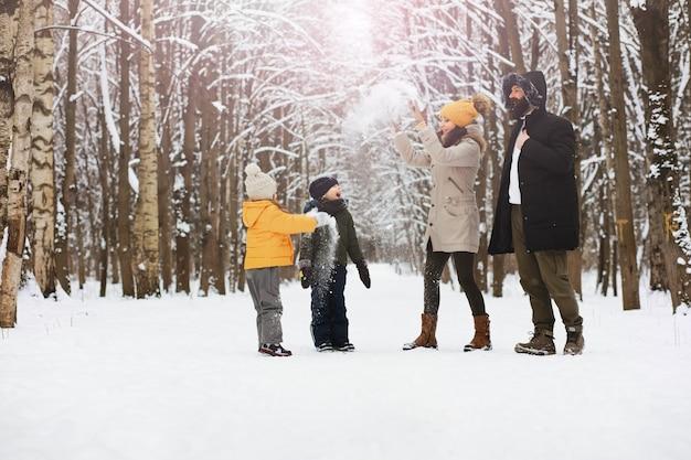 Família feliz brincando e rindo no inverno ao ar livre na neve. dia de inverno do parque da cidade.