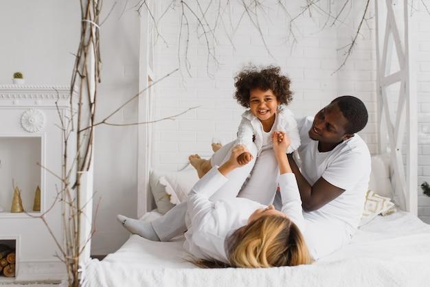 Família feliz brincando na cama com a filha