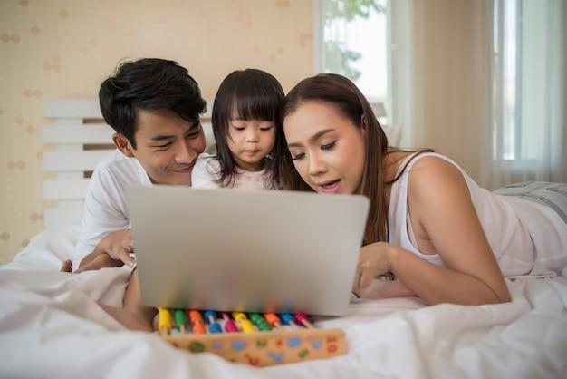 Família feliz brincando na cama