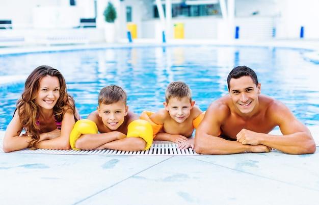 Família feliz brincando na piscina. conceito de férias de verão
