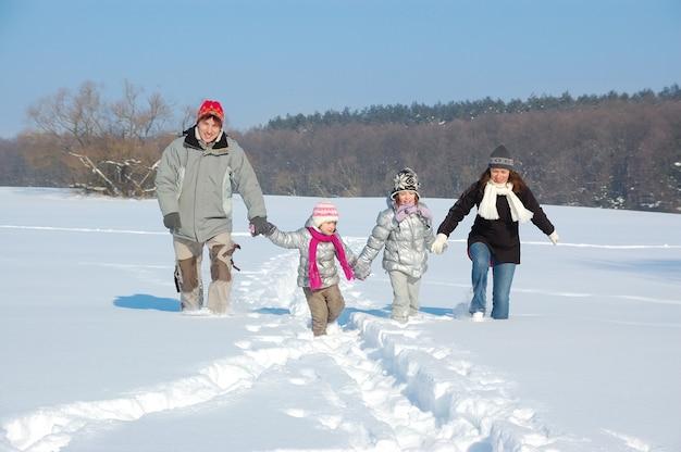 Família feliz caminha no inverno, se divertindo e brincando com neve ao ar livre no fim de semana de férias