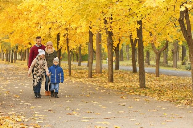 Família feliz caminhando em um lindo parque de outono