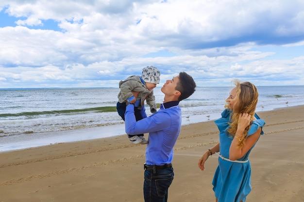 Família feliz caminhando na praia na hora do dia. conceito de família amigável.