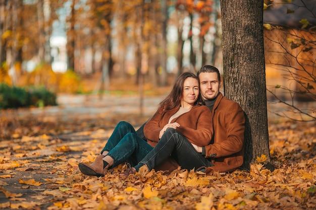 Família feliz caminhando no parque de outono em um dia ensolarado de outono