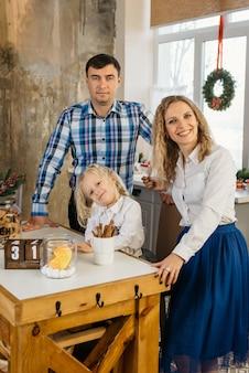 Família feliz caucasiana com criança na cozinha decorada de natal pronta para comemorar em casa. férias de ano novo em clima aconchegante