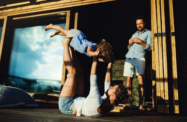 Família feliz com a filha pequena se divertindo no pátio da cabana de madeira, férias no conceito de natureza.