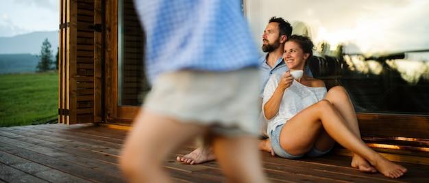 Família feliz com a filha pequena sentada no pátio da cabana de madeira, férias no conceito de natureza.