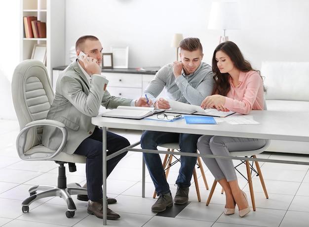 Família feliz com agente imobiliário, em escritório brilhante