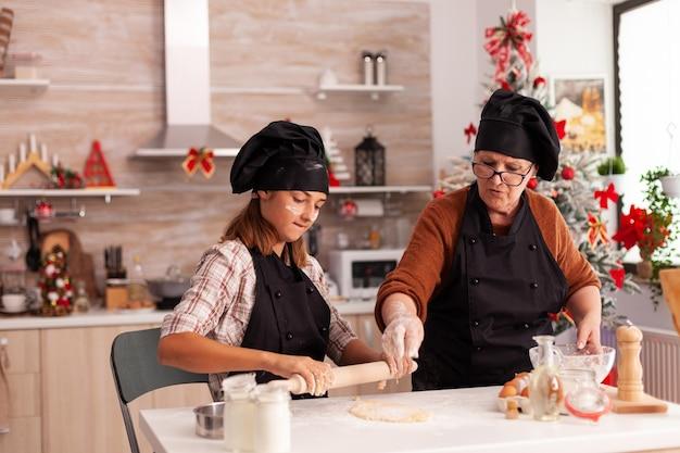 Família feliz com avental preparando massa caseira