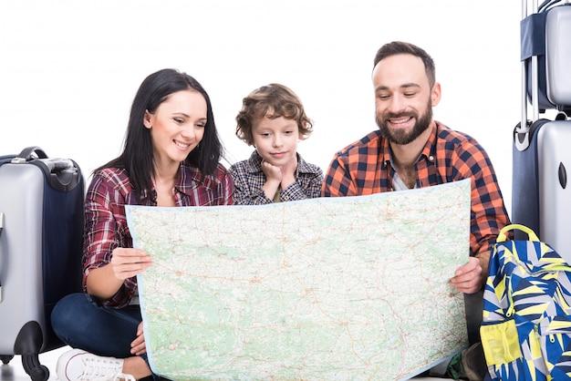 Família feliz com bagagem e mapa estão prontos para viajar.